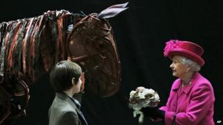 "Queen Elizabeth II receives flowers from a child actor as she inspects the horse prop from the theatre production ""War Horse"" during a visit at the National Theatre in London, Tuesday Oct. 22, 2013 to commemorate the institution's 50th anniversary"