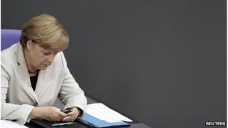 German Chancellor Angela Merkel looks at her mobile in the German parliament, September 2012