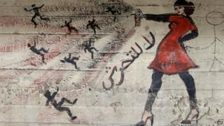 "A mural showing a woman spraying a number of men with the slogan: ""No to harassment"" in Cairo (May 2013)"