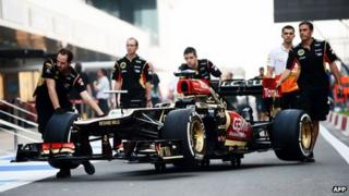Lotus F1 team crew members push the race car used by French driver Romain Grosjean at the Buddh International circuit on 24 Oct 24, 2013
