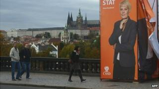 People walk past an election campaign banner of The Czech Social Democrats party (CSSD) on October 17, 2013 in front of the Prague castle in Prague.