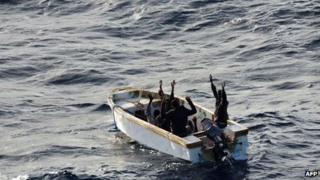 The six Somali pirates in a small motor boat surrender