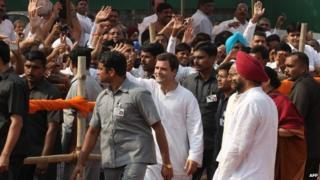 Indian Congress Party Vice president Rahul Gandhi (C,in white) waves towards supporters as he leaves an election rally in Mangolpuri on the outskirts of New Delhi on October 27, 2013