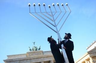 Two Jewish men with a giant Menorah in front of the Brandenburg Gate