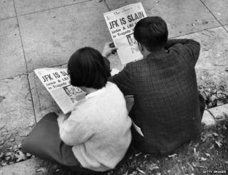 Two people in Lafayette Park, Washington, reading the newspaper reports of President John F Kennedy's assassination