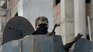 An Indian policeman watches from a armoured vehicle in Srinagar on 7 November 2013