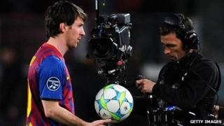 Barcelona's Lionel Messi leaves the pitch after a Champions League game, followed by a cameraman