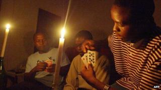 A family plays cards while candles are lit in Harare (21 January 2007)