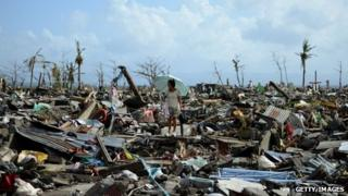 A survivor walks among the debris of houses destroyed by Super Typhoon Haiyan in Tacloban in the eastern Philippine island of Leyte