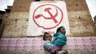 A Nepalese woman carries a child on her back while walking past a political flag and election campaign posters with portraits of Communist Party of Nepal (Maoist) Chairman Pushpa Kamal Dahal, in Kathmandu (31 October 2013)