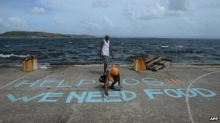 """A man paints a message on a basketball court that reads """"Help SOS We Need Food"""" at Anibong in Tacloban, eastern island of Leyte on 11 November 2013"""