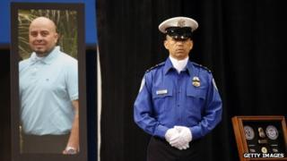 A TSA officer stands in front of a poster of slain TSA officer Gerardo Hernandez during a public memorial for Transportation Security Administration (TSA) officer Gerardo Hernandez at the Los Angeles Sports Arena 12 November 2013