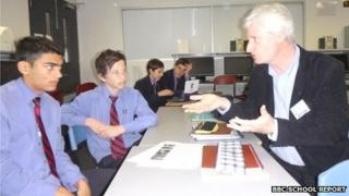Deakin School News Network project leader Paul Bethell in a mentoring session with Nicolas, Matthew, Daniel and Luke from Nazareth Secondary College