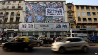 Vehicles journey past a huge banner saluting Indian cricketer Sachin Tendulkar on the facade of a shop in Mumbai on November 13, 2013