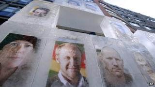 Portraits of Greenpeace activists are frozen in ice cubes in front of the headquarters of Gazprom Germany in Berlin