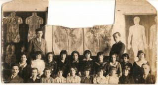 An old photo of a classroom with pupils and two teachers. Part of the photo is cut-out at the top centre.