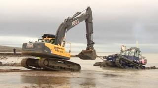 A digger pulling a tractor out of the sea