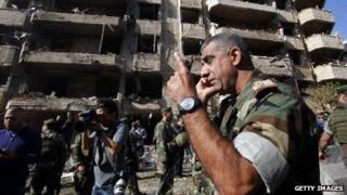 A Lebanese army soldier speaks on the phone in front of the damaged Iranian embassy in Beirut.