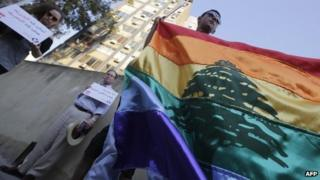 Human rights activists hold up a rainbow flag during an anti-homophobia rally in Beirut in April 2013