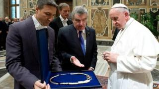 Pope Francis is presented a gift by Thomas Bach, president of the International Olympic Committee, in the Clementine hall at the Vatican on 23 November.