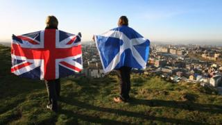 Two people holding up a Scottish and a Union flag