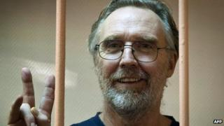 "A handout picture taken on November 18, 2013 and released by Greenpeace International shows Colin Russell making the V-sign for ""victory"" while standing in a defendant cage in a court in Russia's second city of Saint Petersburg"