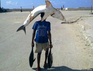 A boy walking on the street with a shark on his head