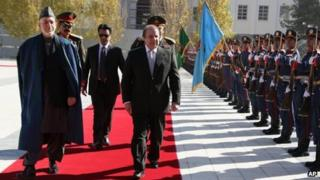 Afghan President Hamid Karzai walks with Pakistan's Prime Minister Nawaz Sharif during a guard of honour ceremony