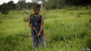 A member of the Guarani Nandeva tribe stands watch at a roadblock they built to keep farmers out, November 22, 2013