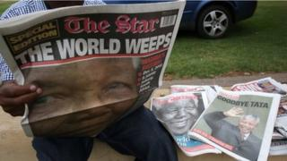 A man reads, in Soweto on December 6, 2013, a local newspaper, The Star, with the front page dedicated to South African former President Nelson Mandela, following his death in Johannesburg on the eve