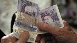 Elderly man holds cash