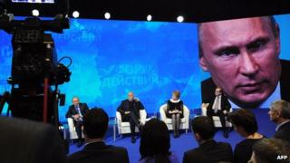 Russia's President Vladimir Putin is seen on a huge screen during a meeting with the All-Russia Popular Front at the Academy of State Service in Moscow on 5 December 2013
