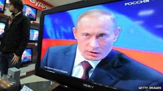 Russian president Vladimir Putin appears on televisions at an electronics store.