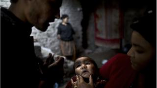 Pakistani Sonya Javed, 20, right, holds her son Shahzeb, 1, to receive a polio vaccine by a health worker at her home in Islamabad, Pakistan, Tuesday, Nov. 26, 2013