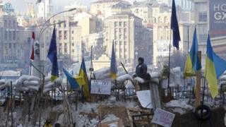 A pro-European integration protester looks out from a barricade on Independence Square in Kiev 14 December 2013