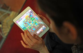 Woman plays Candy Crush Saga on iPad
