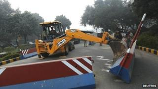 A bulldozer removes the security barriers in front of the U.S. embassy in New Delhi 17 December 2013