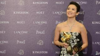 Chinese actress Zhang Ziyi smiles as she displays a trophy after winning the Best Leading Actress award at the 50th Golden Horse Film Awards in Taipei on November 23, 2013.