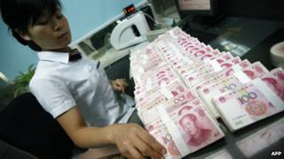 A bank employee counting yuan notes