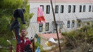 A man tries to dry his clothes one the fence of the migrant reception centre on Lampedusa (October 2013)