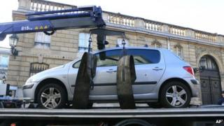 A car is towed away after a driver tried to ram it through a gate of the presidential Elysee Palace on 26 December, 2013.