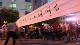 """This picture taken on July 17, 2013 shows people walking on street to protest after a fruit seller Deng Zhengjia died in Linwu county, central China""""s Hunan province."""