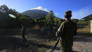 Soldiers stand guard as the Chaparrastique volcano spews ash on 30 December, 2013