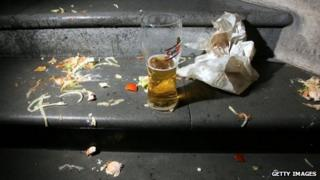 Discarded pint glass and fast food wrapper