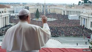 """Pope Francis waves as he delivers his first """"Urbi et Orbi"""" message from the balcony overlooking St Peter's Square at the Vatican (25 Dec 2013)"""