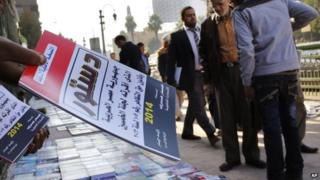 An Egyptian distributes copies of the new constitution on a street in Cairo, Egypt