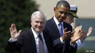 Retiring US Defence Secretary Robert Gates acknowledges applause as he stands next to President Barack Obama in Washington 30 June 2011