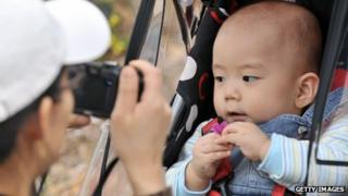 A South Korean parent takes a photo of a baby in Seoul