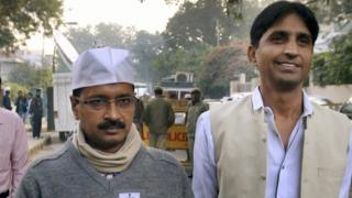 Arvind Kejriwal leader of the Aam Aadmi Party, or the Common Man's Party, displays his voter identification card as he arrives to cast his vote for the Delhi state assembly elections in New Delhi, India, Wednesday, Dec. 4, 2013.