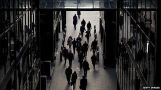 City workers walking past buildings in shadow